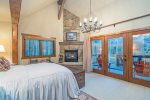 Master bedroom with queen-sized bed, gas fireplace and deck with amazing views