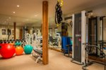 Home gym with Cybex Full Body Training System, fitness balls, free weights, flatscreen TV, and Direct TV
