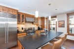 The fully-equipped kitchen has stainless steel appliances, and breakfast bar seating for 3
