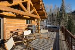 Large deck located off kitchen with BBQ grill, a hot tub, outdoor seating, and views of the Village Bypass Ski Run
