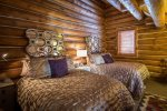 This guest bedroom has two full-sized beds and an en suite bathroom