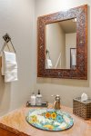 The half bathroom downstairs continues to showcase Southwestern flair with a hand-painted sink