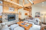 Incredible living area with vaulted ceilings, wooden beams, and a stone fireplace