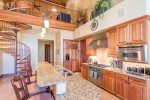 Fully-equipped gourmet kitchen with stainless steel appliances and breakfast bar seating for 4