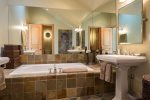Luxurious en suite master bathroom with jetted tub, steam shower, double sinks