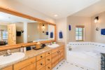 The master bathroom has a double vanity and a large soaking tub