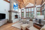 Designer-decorated living room with big windows and a gorgeous stone fireplace