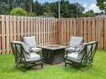 Private fenced in yard with outdoor seating, string lights, fire pit, and grill