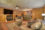 Lower Level Game Room with a Pool Table, Wet Bar, Sofa, Chair, Large Flat Screen TV, and a Gas-Log Fireplace