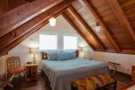 Cozy loft bedroom has a king-sized bed