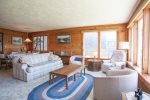 Large windows line the living room and offer a peek ocean view