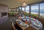Living and dining rooms look toward a panoramic view of the ocean