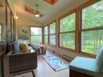 Enclosed sun room off of the living room with partial Whitefish Lake views and views of the stream