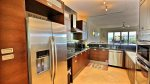 Kitchen with stainless appliances, dark cabinetry, elegant granite