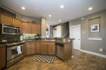 Fully equipped kitchen with stainless steel appliances, breakfast bar for 2