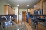 Fully equipped kitchen with gas range, four gas burners, stainless steel appliances