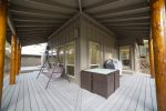 Large wrap around deck with seated dining, porch swing and natural gas barbeque