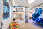 A fun kids room featuring custom built bunk beds with slide