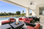 The outdoor pool deck features comfortable relaxation furniture, a summer kitchen and dining space.