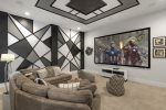 Modern meets retro in this theater room with a large projection screen