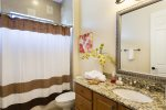 The ensuite bathroom has a combination shower and tub with granite counters