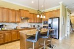 The fully equipped kitchen has stainless steel appliances and seating around the island