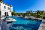 This expansive home has a large pool deck for your next luxury vacation.