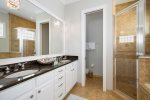 The en-suite bathroom features dual vanity and walk-in shower