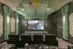 It features a 119-inch projection screen , Apple TV 2, Smart DVD player, seating for up to 12, and 4 bean bags
