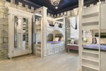 The princess castle themed kids bedroom has custom built twin over twin bunk beds
