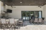 The covered lanai features a summer kitchen, 50-inch TV, and outdoor dining table