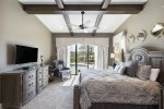 This master bedroom provides a large TV and private access to the patio