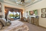 The master suite features a king size bed, SMART TV, access to pool area, and en-suite bathroom