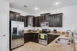 Custom kitchen cabinetry, marble countertops and stainless steel appliances