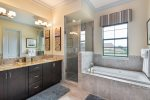 The en-suite bathroom has glass door walk-in shower, tub, and dual vanity