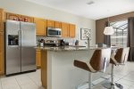 The kitchen features stainless steel appliances and breakfast bar
