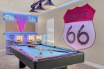 The room features a fun theme complete with custom artwork and a pool table