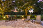Comfortable patio furniture including a table for four next to the fire pit