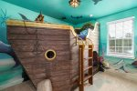 Little pirates will love this fun bedroom with a pirate ship bed and under the sea artwork