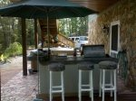 The Outdoor Kitchen Features a Grill and Burners and Outdoor Fridge