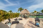 Backyard is vacation ready with a Tiki Hut, water views, lounge chairs