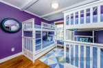 High end wood bunk beds with beach themed pillow and linens. Great place for the kids to have their space.