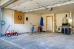 The garage has room to park a car,  outdoor furniture, and a dart board.