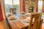 Have a family style meal at this dinner table with ocean views, near the fire place.