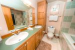 The master bathroom has a double vanity sink and large tub to soak in.