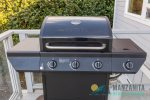 Gas grill with propane included near kitchen for easy access.