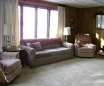 Living room on upper level has sleeper sofa and TV; opens to upper level deck