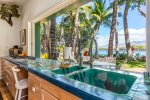 This one of a kind kitchen dining area looks back at Beach 69 on the sunny Kohala Coast of the Big Island