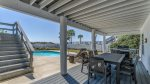 A large 6 burner gas grill & dining table accent the pool deck