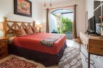 Guest bedroom 2 with queen bed and private pool view terrace.
